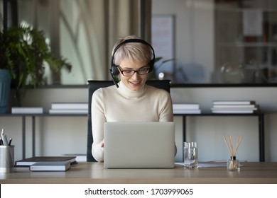 Smiling Caucasian businesswoman sit at desk in office talk on webcam with business client wearing headset, middle-aged woman in headphones have video call consult customer online on laptop