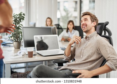 Smiling Caucasian CEO sitting at office and talking to employee. In backgrounds employees working.