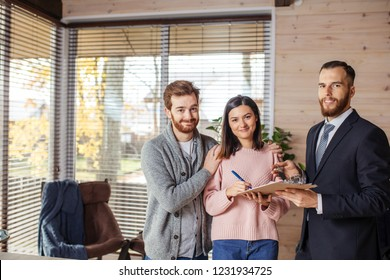 Smiling caucasian couple of attractive tenants shaking hands with landlord, receive house key, making rent deal