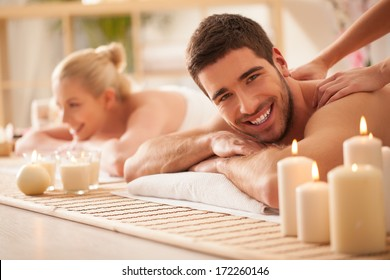 Smiling Caucasian couple enjoying a back massage.