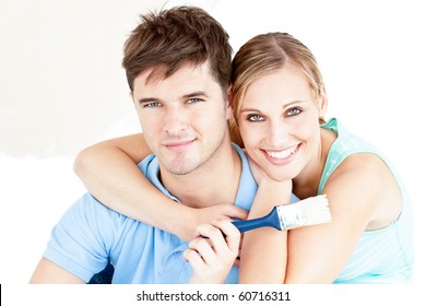 Smiling Caucasian Couple Painting A Room In Their New House
