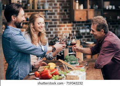 smiling caucasian friends drinking wine while cooking dinner
