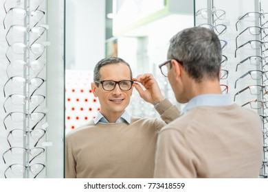 smiling caucasian man choosing pair of eyeglasses in optics
