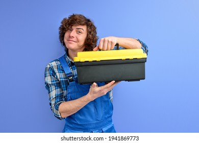 Smiling caucasian man in coveralls opening tool case box isolated on blue studio background