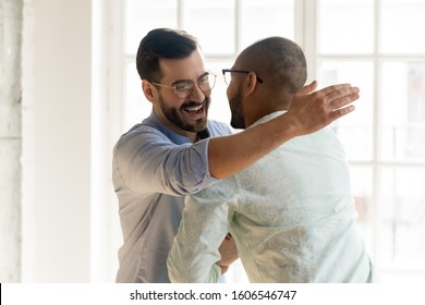 Smiling Caucasian man in glasses feel overjoyed meeting ethnic male friend or colleague, happy young multiethnic guys hug embrace tapping shoulder excited encounter at party, friendship concept