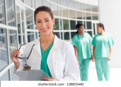 Smiling caucasian nurse holding a clipboard in brightly lit exterior hospital environment in scrubs, white lab coat and holding glasses.Two nurses in scrubs in the background.