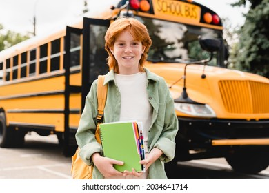 Smiling caucasian redhead schoolgirl going back to school with books and copybooks waiting for schoolbus. New academic year semester