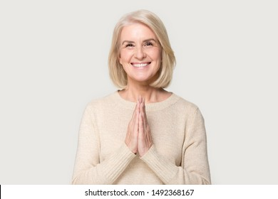 Smiling Caucasian senior woman isolated on grey studio background hold hands in prayer show hope and belief, happy aged female look at camera say Namaste religious greeting, body language concept