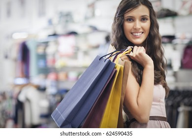 Smiling Caucasian woman holding shopping bags at a clothing store.