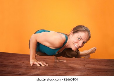 Smiling Caucasian woman performs yoga on a wooden mat