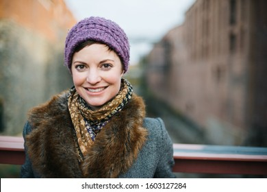 Smiling Caucasian woman portrait smiling and looking at the camera head and shoulders dressed in warm clothing wearing a knit hat and standing on a bridge over the canal in Georgetown, Washington DC.