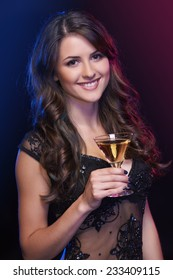 Smiling celebrating woman with a cocktail