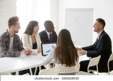 Smiling ceo talking to multiracial team at office meeting, friendly executive discussing good news laughing at group briefing negotiations, coach mentor joking speaking to business people at training