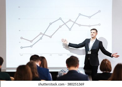 Smiling charismatic speaker giving public presentation in conference hall