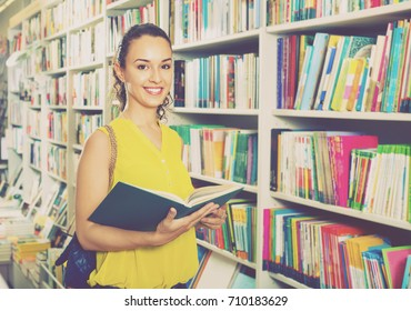 Smiling charming beautiful glad woman standing with open in publishers store