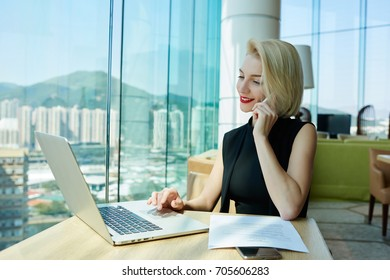 Smiling charming businesswoman in elegant outfit confirming booking on website communicating on phone in good mood,prosperous female entrepreneur satisfied with receiving transaction for project