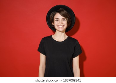 Smiling cheerful beautiful attractive young brunette woman 20s years old wearing casual basic black t-shirt hat standing and looking camera isolated on bright red color background studio portrait