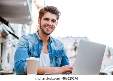 Smiling cheerful casual man using laptop while sitting at cafe outdoors at lunch break