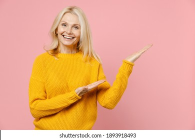 Smiling cheerful elderly gray-haired blonde woman lady 40s 50s years old in yellow casual sweater pointing hands aside on mock up copy space isolated on pastel pink color background studio portrait