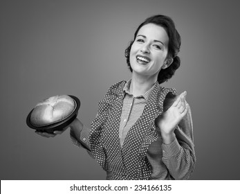 Smiling cheerful female cook showing an handmade cake in a baking tin