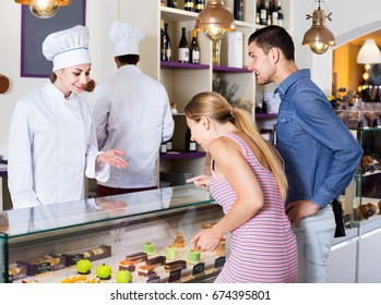 Smiling cheerful  female pastry chef helping customers to choose pasrties in comfortable cafe