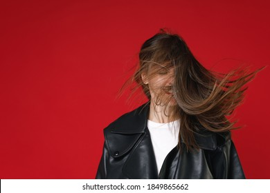 Smiling cheerful funny young brunette woman 20s in black leather jacket white t-shirt standing shaking head with flowing hair keeping eyes closed isolated on bright red background studio portrait
