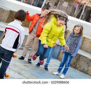 Smiling cheerful girl jumping while jump rope game with friends outdoor