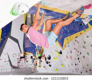 Smiling cheerful  glad positive male alpinist practicing indoor rock-climbing on artificial boulder without safety belts