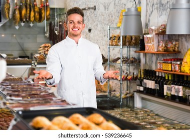 Smiling cheerful glad shop assistant in grocery shop greeting customers