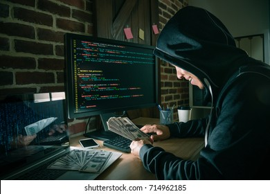 smiling cheerful hacker man using code program system getting many business information and blackmail a lot of banknote money.