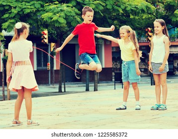 Smiling  cheerful kids in school age playing together with jumping rope outdoors