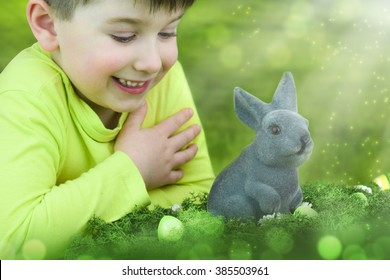 Smiling cheerful little boy with bunny toy at spring time in the meadow.