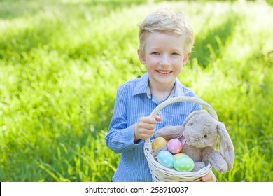 smiling cheerful little boy holding basket with colorful easter eggs and bunny toy at spring time in the park