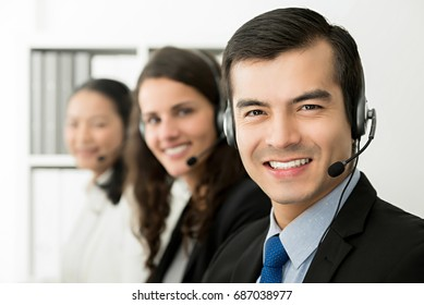 Smiling cheerful male telemarketing customer service agent with his team, call center job concept