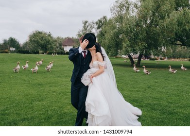 Smiling and cheerful newlyweds walk and kiss on the background of green grass in the park, hiding behind a hat. Wedding portrait of a stylish bride and groom with curly hair and white dress.
