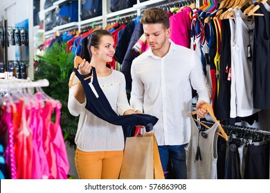 Smiling cheerful positive couple examining various sports clothes in sports store