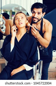 Smiling cheerful positive man makeup artist applying cosmetics for woman talking phone