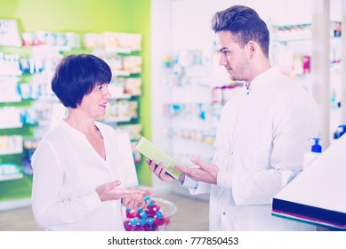 Smiling cheerful positive man pharmacist wearing uniform assisting customers in pharmaceutical shop