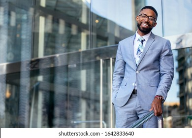 Smiling cheerful successful African American CEO businessman in stylish modern suit, happy warm distinguished portrait