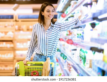 Smiling Cheerful Woman Walking With Shopping Trolley Cart Along The Shelves In Grocery Store. Happy Lady Buying Groceries In Supermarket, Taking Dairy Products Standing Near Fridge Aisle