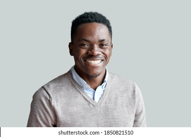Smiling cheerful young adult african american ethnicity man looking at camera standing at home office background. Happy confident black guy posing for headshot face front close up portrait.