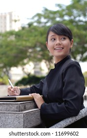 Smiling and cheerful of young business woman signing the document.