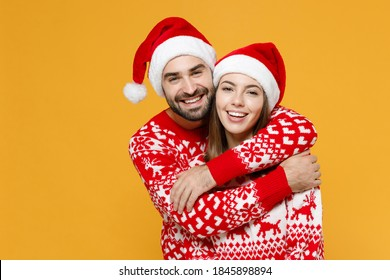 Smiling cheerful young Santa couple friends man woman 20s wearing red sweater Christmas hat hugging isolated on yellow background studio portrait. Happy New Year celebration merry holiday concept