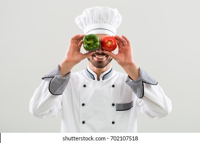 Smiling chef is covering his eyes with tomato and pepper on gray background.Happy chef with vegetables