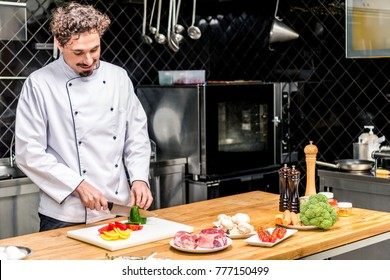 smiling chef cutting colored bell peppers