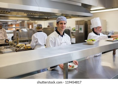 Smiling chef garnishing a salad in the restaurant