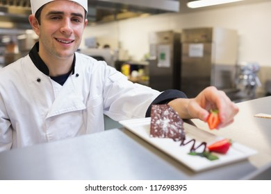 Smiling chef garnishing a slice of cake in the kitchen