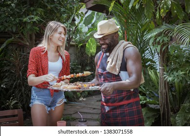 Smiling chef give barbecue to female friend for dinner camping in nature outdoor as summer lifestyle