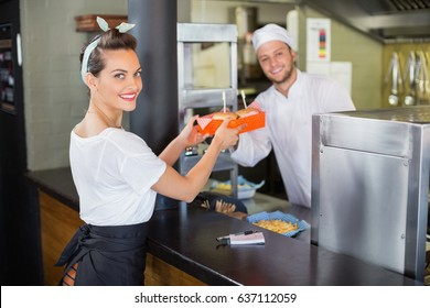 Smiling chef giving burgers to waitress in commercial kitchen