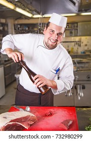 Smiling chef holding pepper dispenser, looking at the camera. Cooking board with a big piece of raw meat. Putting spice on raw meat. Chef preparing meat in the kitchen of the restaurant